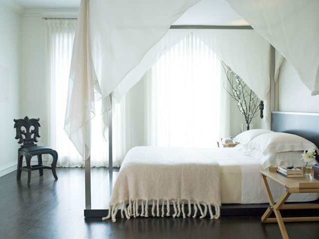 Kara Mann's four-poster white bed floats serenely in this Chicago Lakeshore penthouse space.