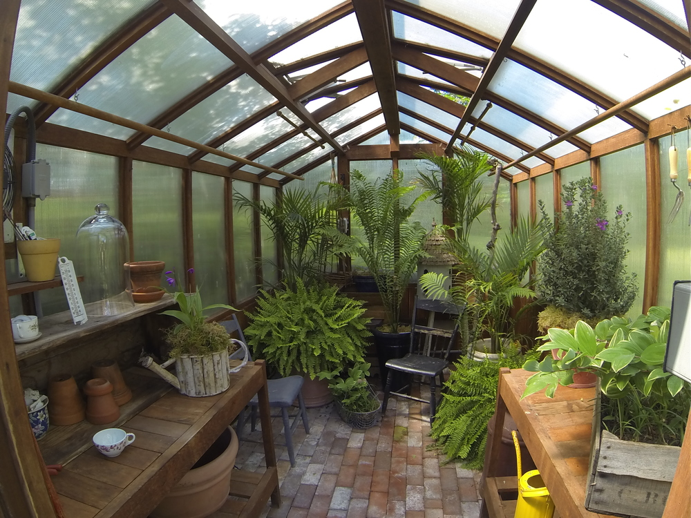 A cozy greenhouse behind the hunter's lodge preps Solomon's seal, ferns, and rose of sharons for planting.