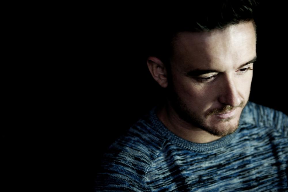 Matt Tolfrey sitting in a dark room. Humming probably.