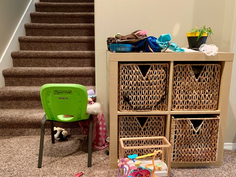 The basket has overflowed with items that need to make their way up the stairs.