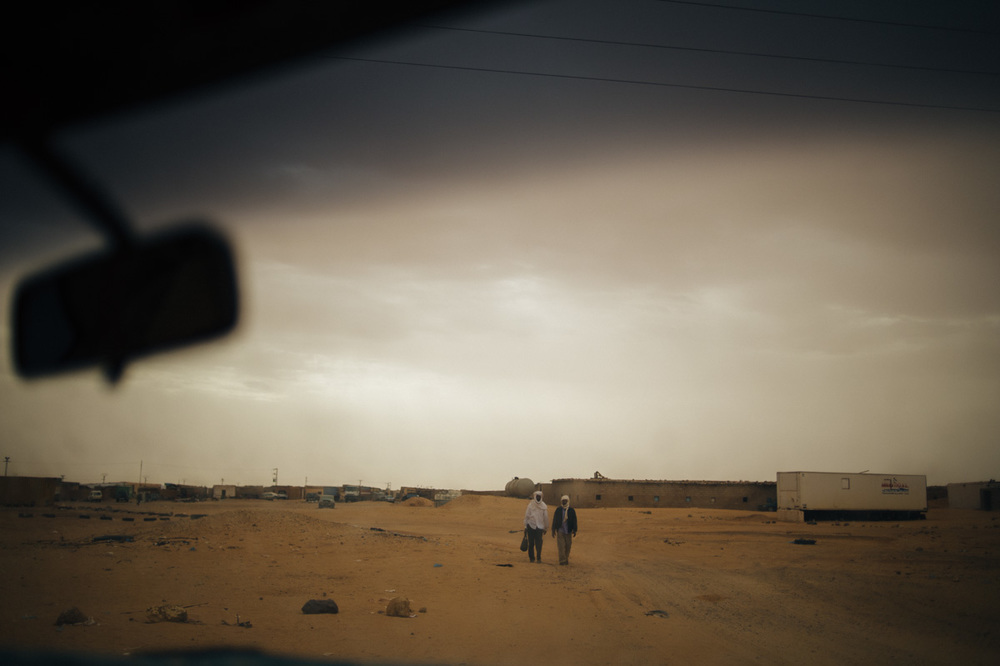 Men walking on their way to the main World Food Program warehouse in Rabouni.