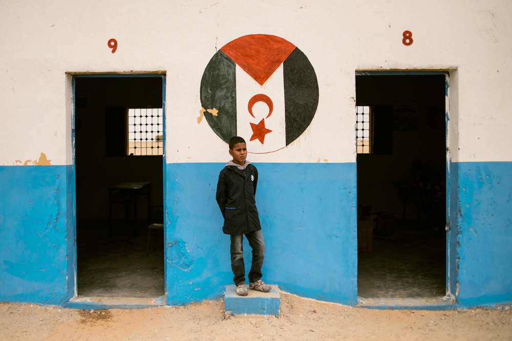 Sahrawi students as they waiting in line for UNICEF-donated supplies on the first day of school; a Sahrawi boy poses under a painting of the SADR flag in his schoolyard.