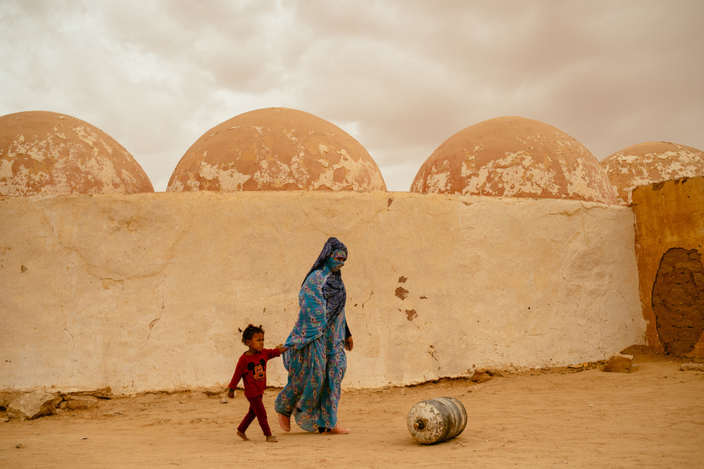 The road to Laayoune; a mother and daughter with an empty propane tank.