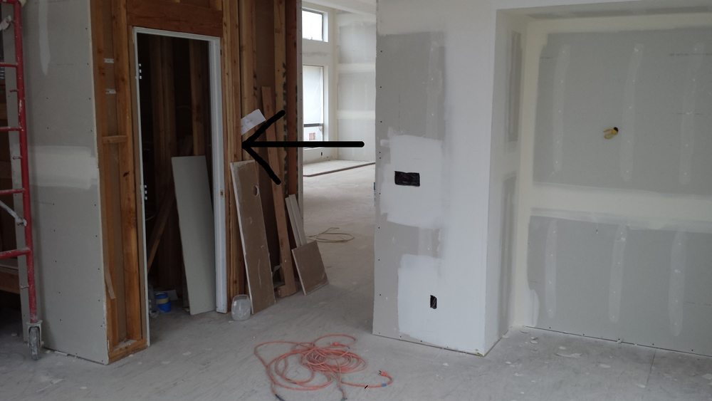 It is much easier to hang the doors without any drywall. However, to keep construction moving forward, the drywall is left off around the openings. After the door(s) is hung, the drywall will be finished up to the door opening.