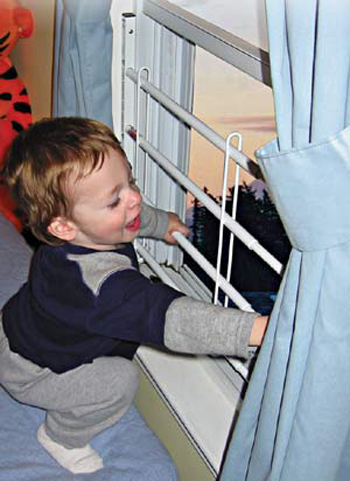 A toddler test the safety bars on a window.