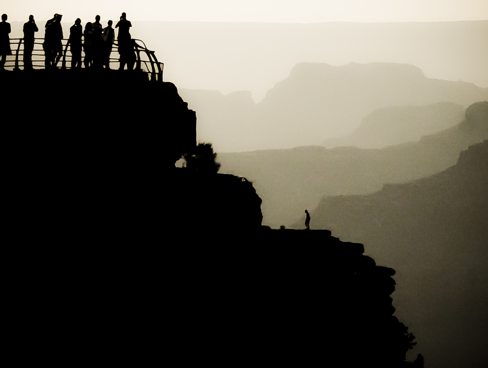 A primitive looking man walks freely on the rim of the Canyon enjoying the view below a sea of tourists securely gated above.