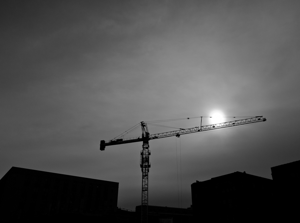 A large construction crane rises into the sky above the city appearing to move the sun.