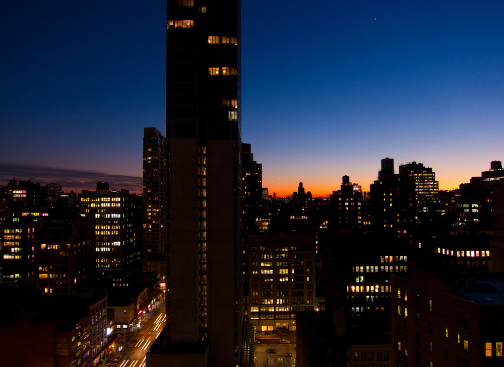 The first star of the night becomes visible in the dark blue sk above the buildings of Manhattan.