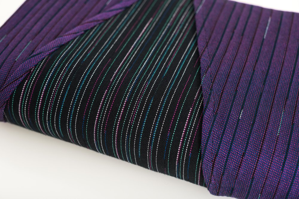 Duet Violet · 100% cotton  Duet Violet is a medium thick, densely woven wrap that shines in various sizes. Duet has the perfect amount of glide to allow you to makes passes and enough grip to lock them in place. The dense weave of Duet also makes it a great no-fuss on the go wrap. In a shorty, it can give you excellent support with a single layer carry; while in a base size, this wrap is a workhorse for toddlers and heavier babies.