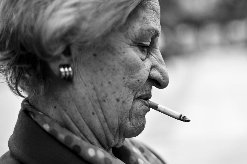 A woman smokes and eats pistachios on a bench in Sindagma Square in Athens, Greece on September 16, 2012. Sindagma Square, one of Athen's most famous public spaces, is now graffiti and litter strewn .