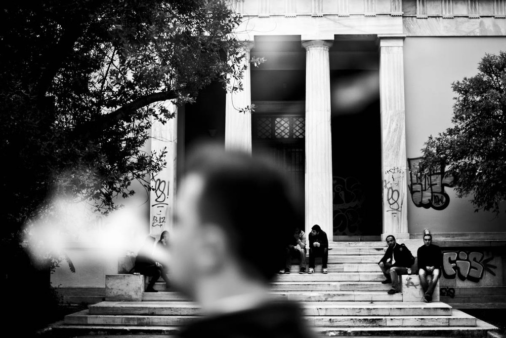 A man smokes a cigarette at a gathering at the Athens Polytechnic commemorating the 1973 student uprising against the military dictatorship on November 16, 2012.  This year, the commemoration is charged with anger and frustration over current political and economic situation in Greece.