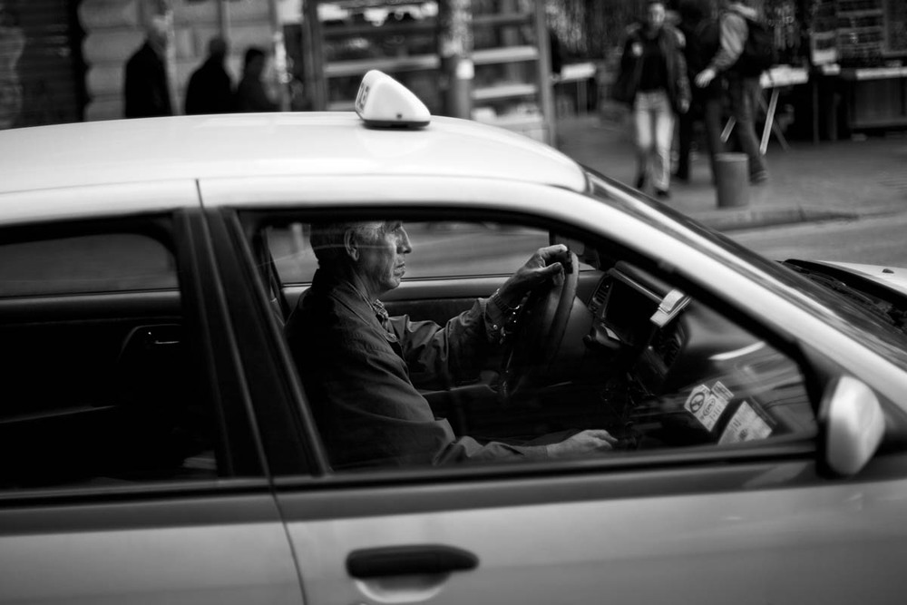 A taxi driver waits for customers in Omonia Square in Athens, Greece on November 16, 2012. It used to be difficult to hail a taxi in Greece, but now they line the streets in the hopes of getting some business.