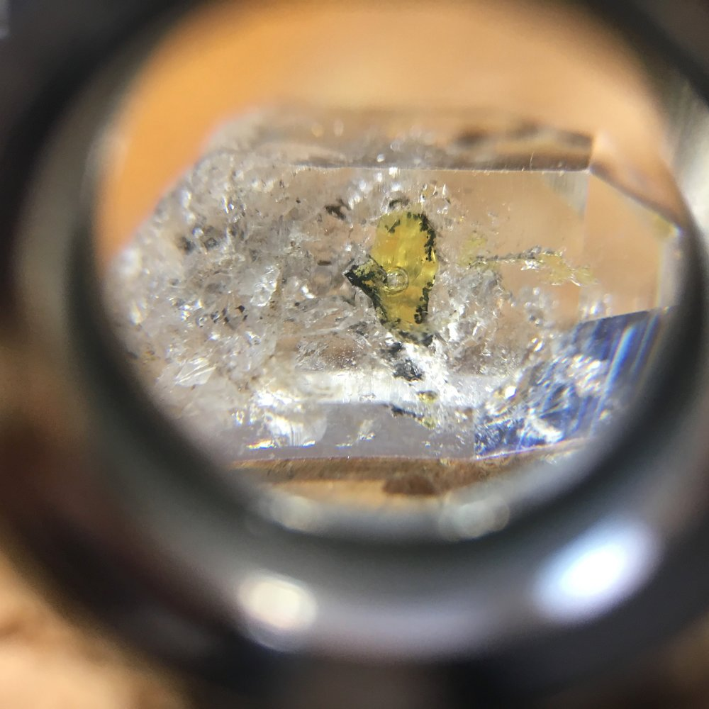Detail view of golden enhydro quartz also known as petroleum included quartz under 10x magnification of a jeweler's loupe. Note the tiny air bubble within the golden yellow petroleum inclusion. Photo credit: Michelle Pajak-Reynolds