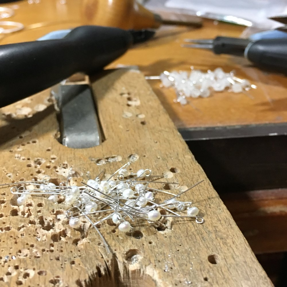 A pile of pin-set seed pearls for a new design sits on Michelle Pajak-Reynolds's jewelry workbench. Photo credit: Michelle Pajak-Reynolds