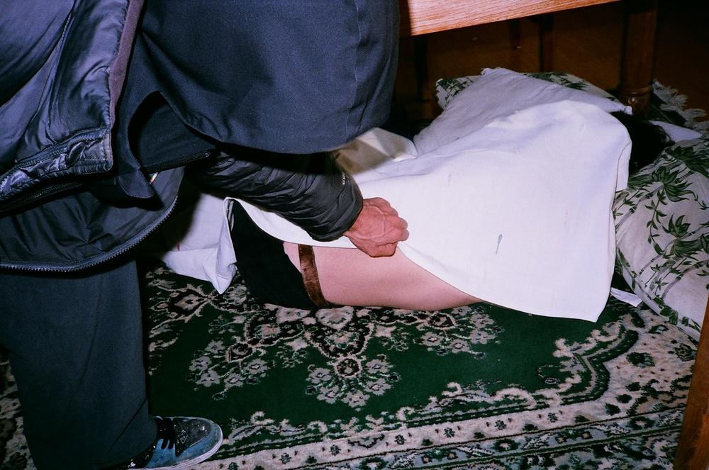 "Alter ego ""Corey Marshall"" sleeps under a table, using a curtain as a blanket."