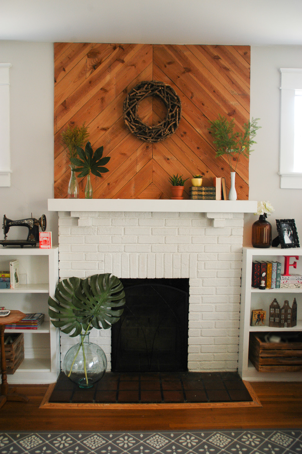 We added these wood slats to the fireplace to create some texture and height. Bonus: it didn't cost us anything! We had some old wiring that needed to be removed in the attic, and had to rip up a bunch of boards to get to them. Instead of throwing it all away, we just reused it inside the house! How's that for recycling?