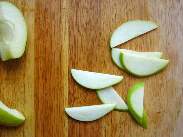 Using your chef knife, cut each quartered apple into slices, about 1/4 in thick.