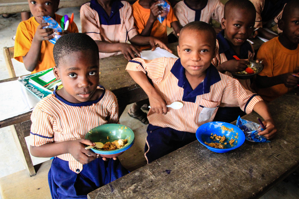 Children enjoying their hot, nutritious meal for the day in the community of Ilaje.