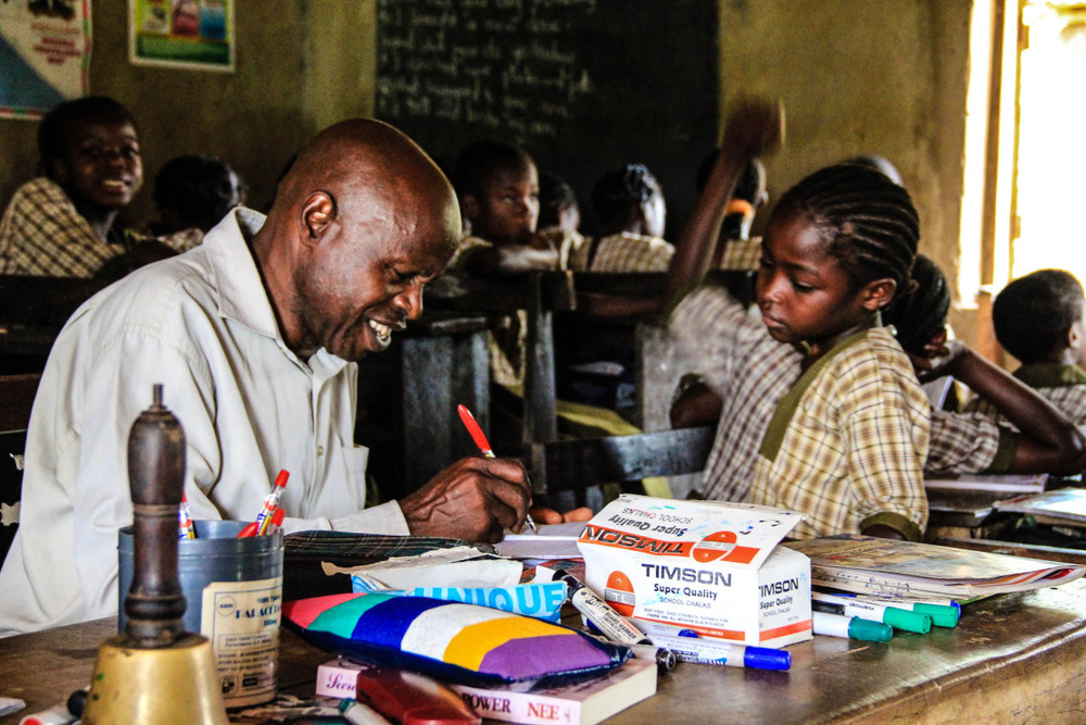 "Teacher Philip, from Elekuru Community School, lovingly grading one of his student's papers. ""It brings me great joy to teach,"" says Philip."