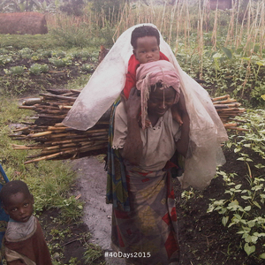 A grandmother Goma carrying a child as she works.