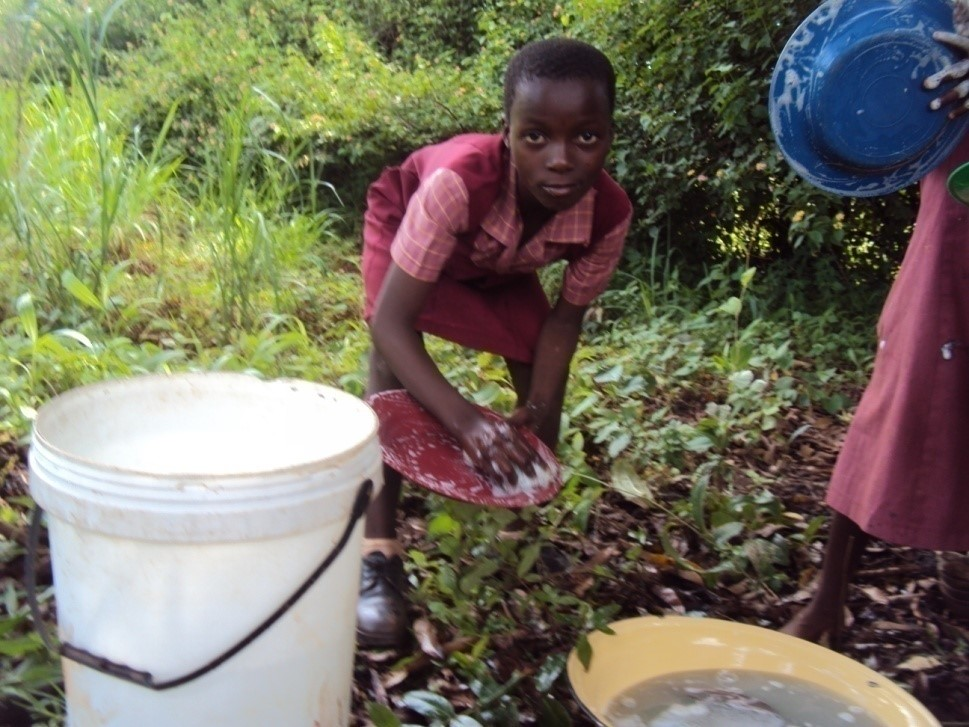 Nomsa helps her Care Workers clean dishes after her daily meal at the local Care Point in Honde Valley