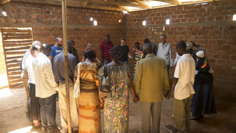 Praying in a village with Care Workers, local leaders, and international visitors