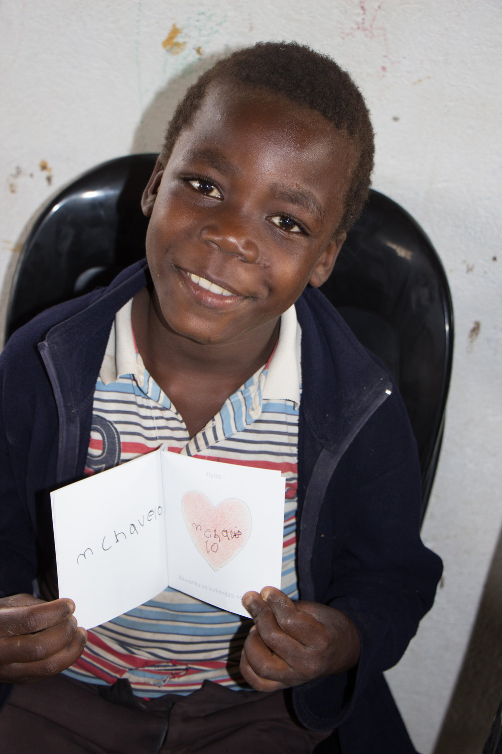 """This photo is of Josefa* from Pfunani Community.  We were doing an appreciation day for the Care Workers and because there was an additional workbook left over, I gave it to Josefa and asked him to write his name on the heart. The booklet was based on Ephesians 3:18 and when I explained that it said 'God loves Josefa,' he gave me a huge, beautiful smile."""