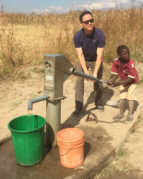 Stephen helps a boy pump water at the Mcheneke Care Point.
