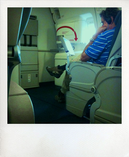 photo from on board my flight home - man watching his screen