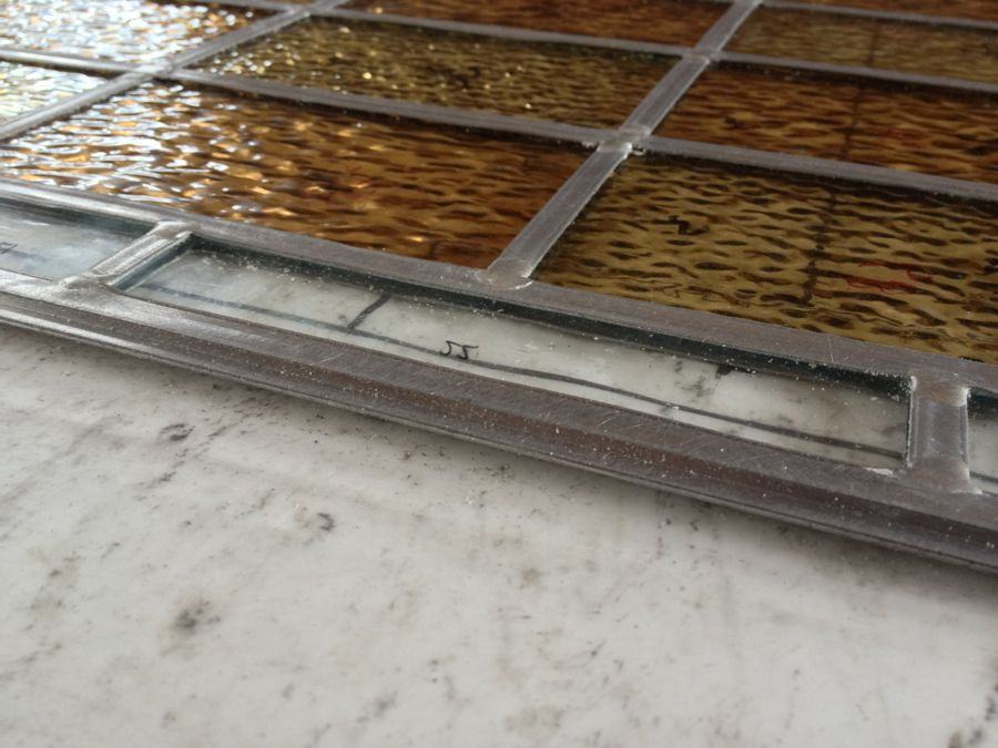 """Y-shaped lead around a panel for encapsulation. Spacers around the edge of the double glazed unit grip the """"flange""""."""