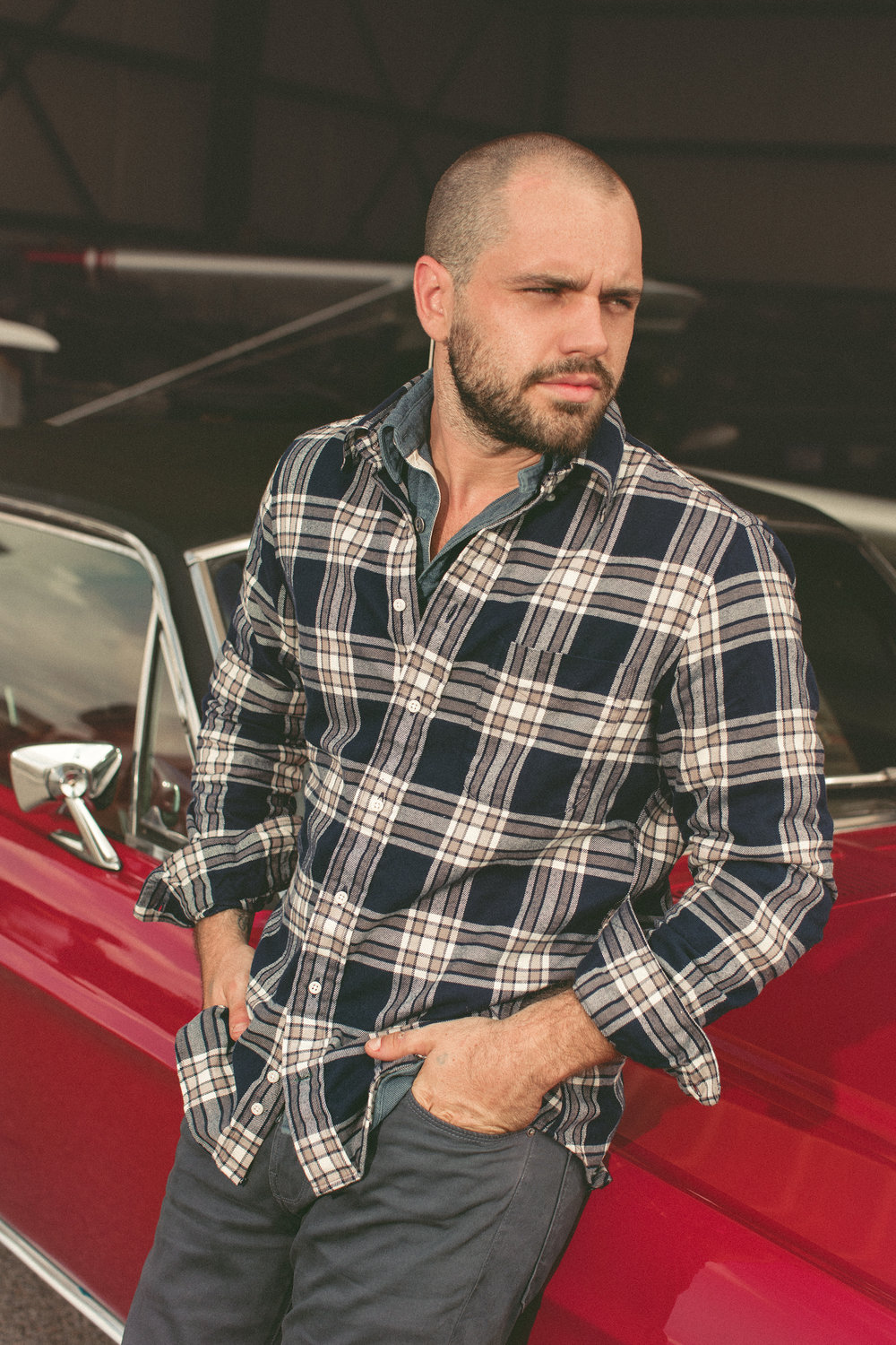Male model in plaid shirt leaning against vintage mustang