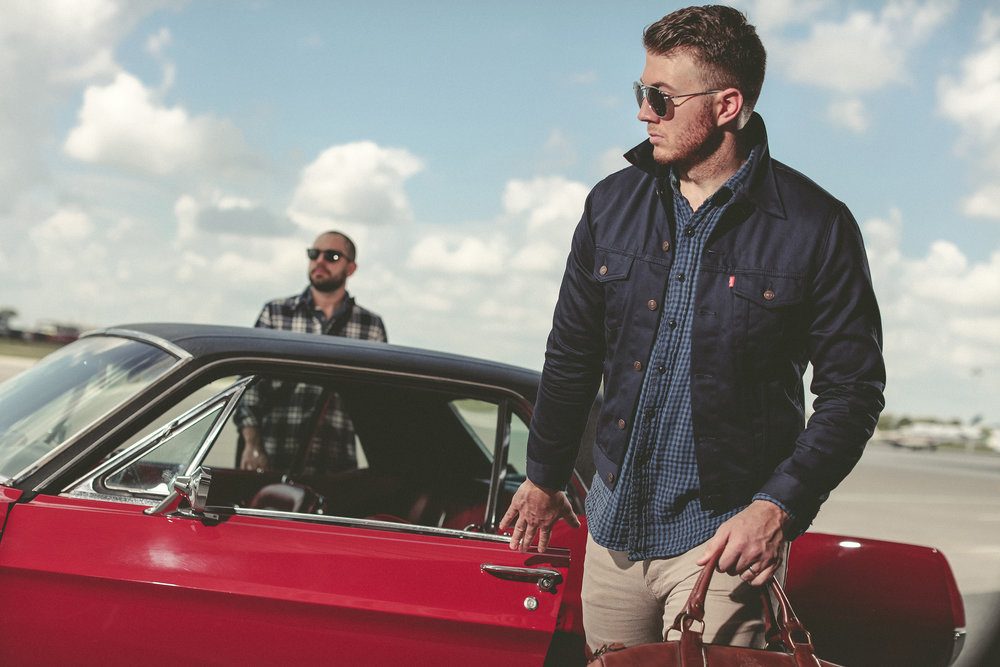 White male models with red vintage mustang