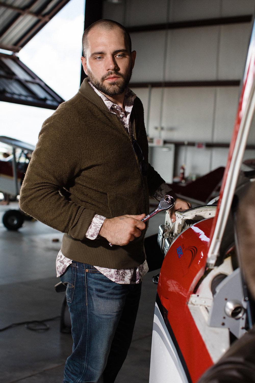 Male model in sweater in airplane hangar