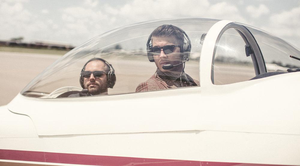 Male models in vintage airplane cockpit