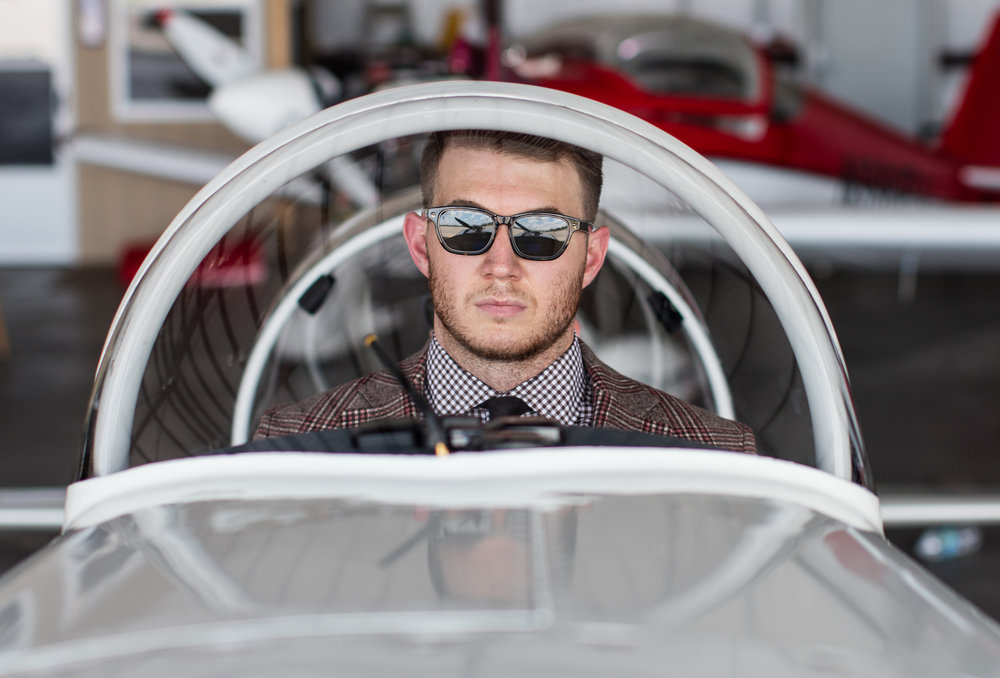 Male model in suit and sunglasses in vintage airplane