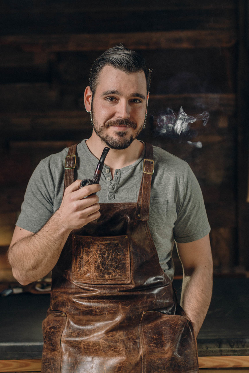 Artisan woodworker portrait with pipe smoking