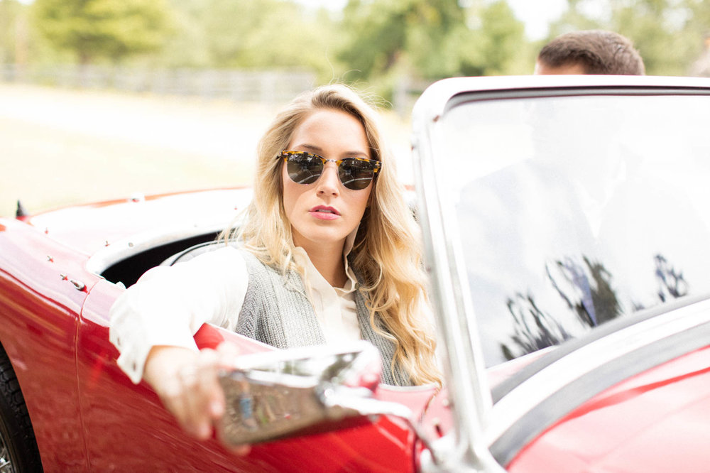 Female fixing mirror on vintage red convertible