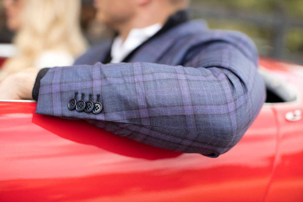 Male in plaid suit with buttons driving vintage red convertible