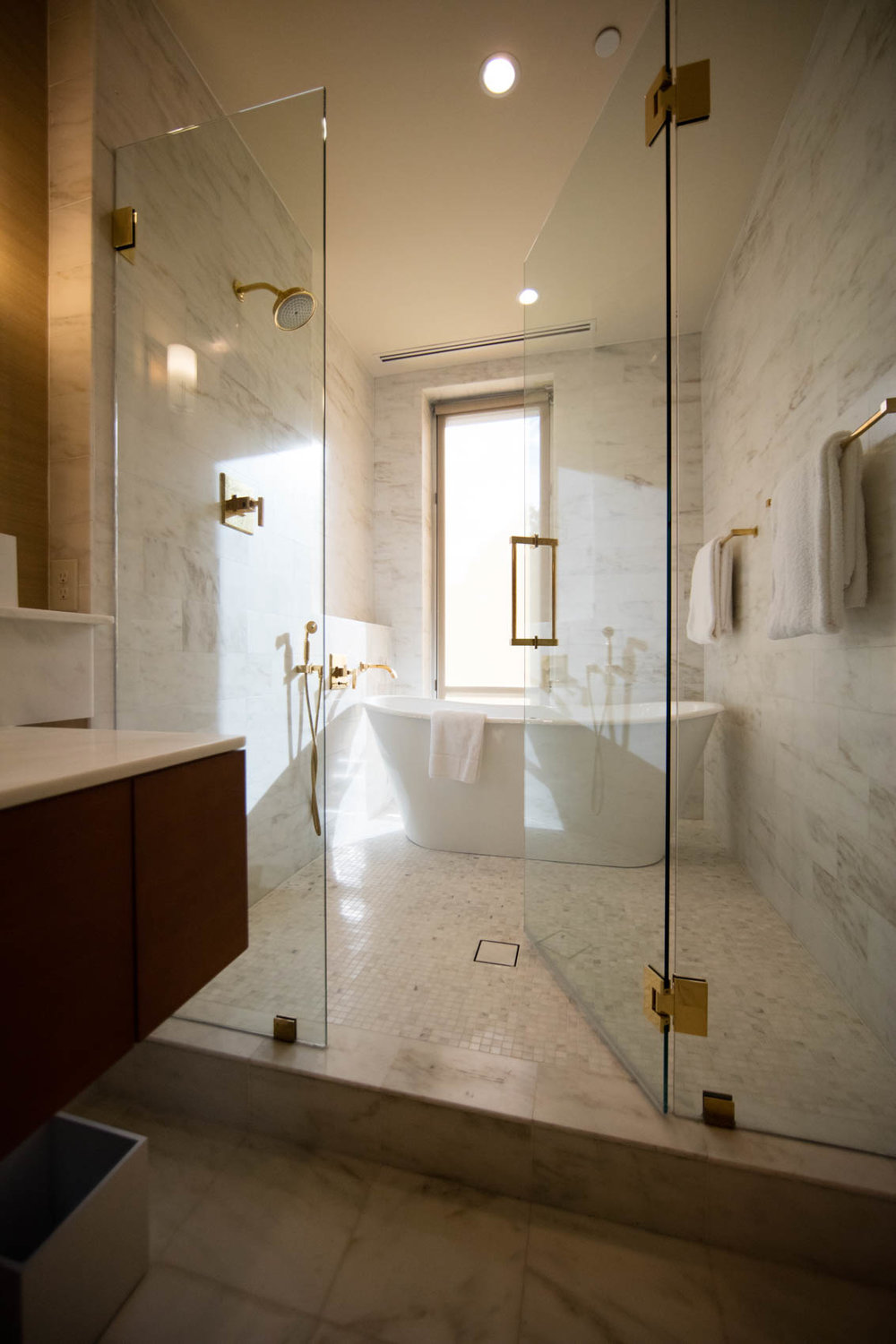 marble bathroom with glass shower doors and soaker tub
