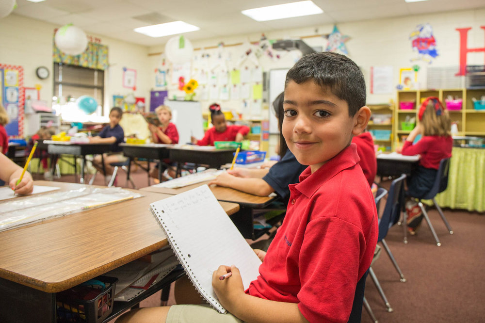 elementary school student smiling at desk
