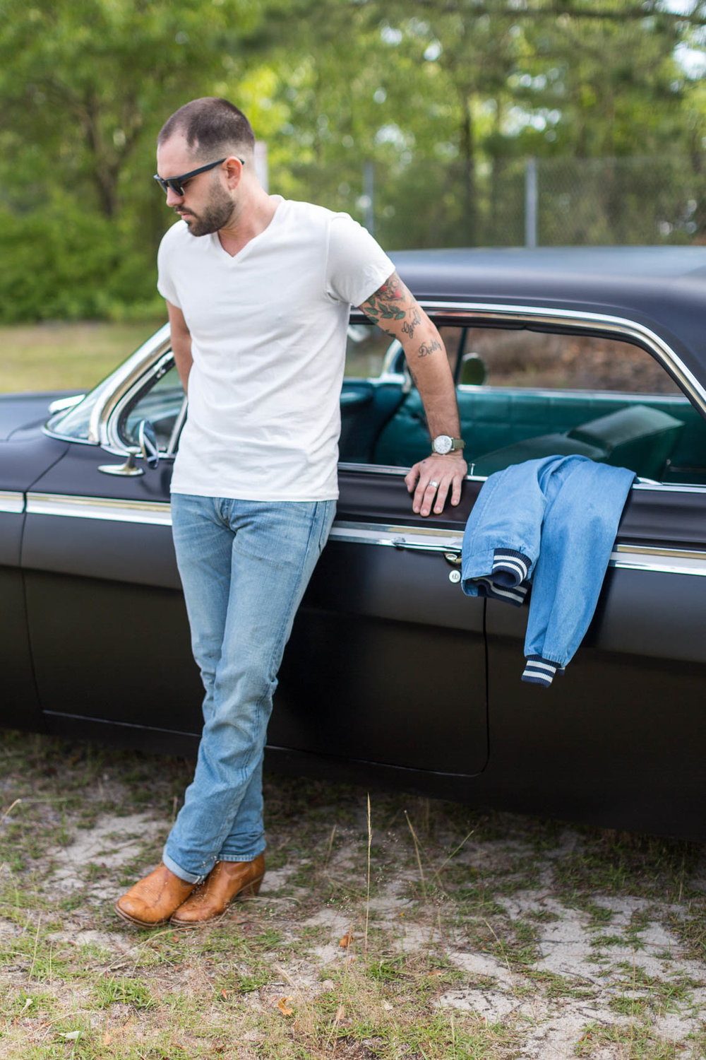 American male with tattoos leaning against vintage car