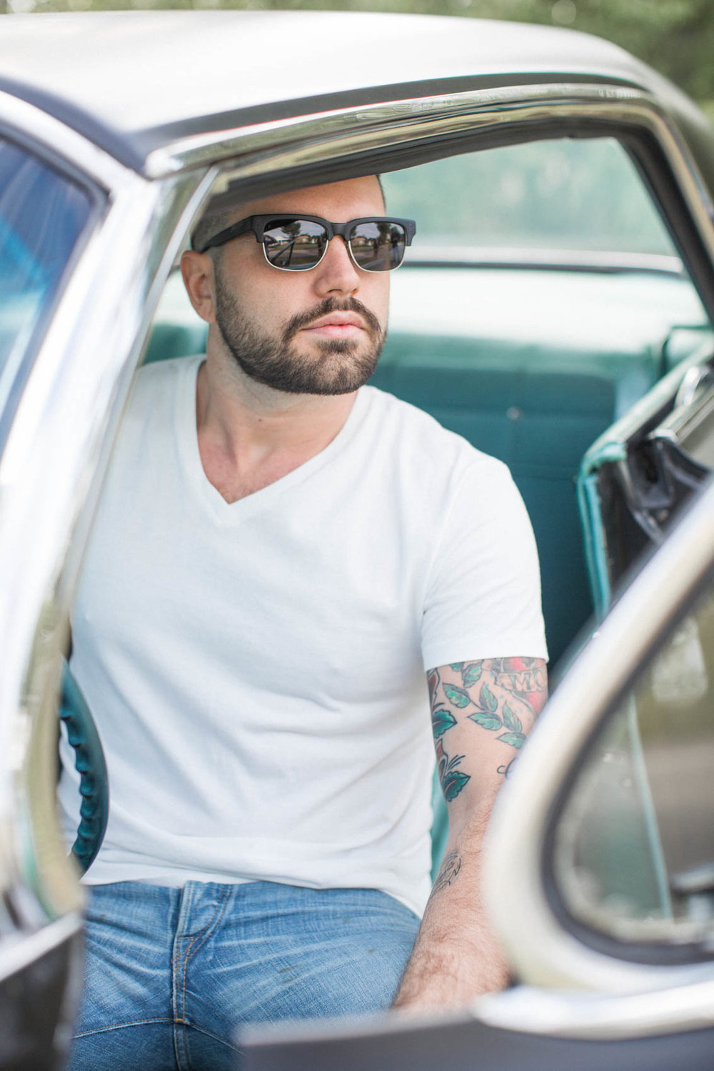 American white male with tattoos driving vintage car
