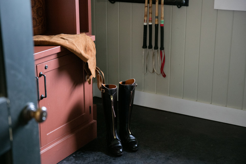 Horse barn riding boots in mudroom