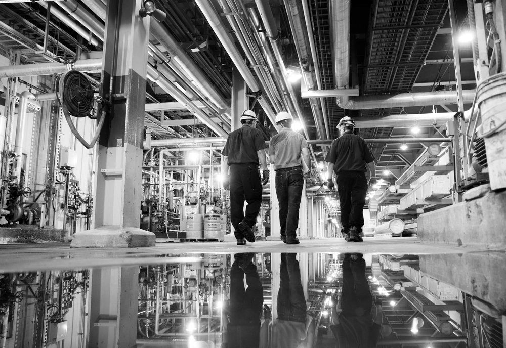 Male workers walking in industrial warehouse
