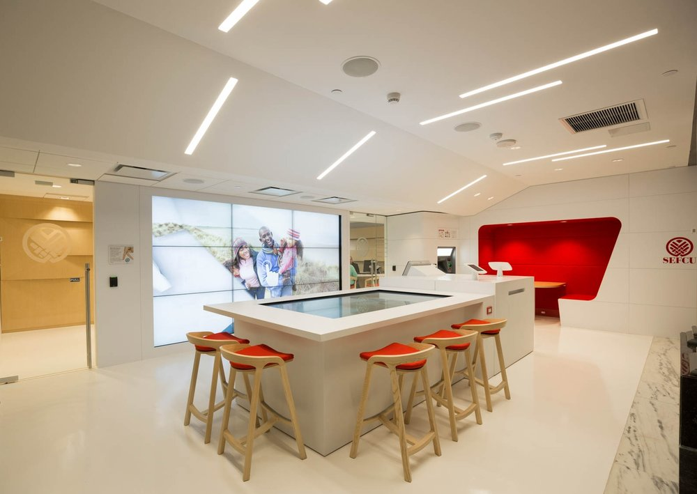 Modern bank with red chairs and large tv screen