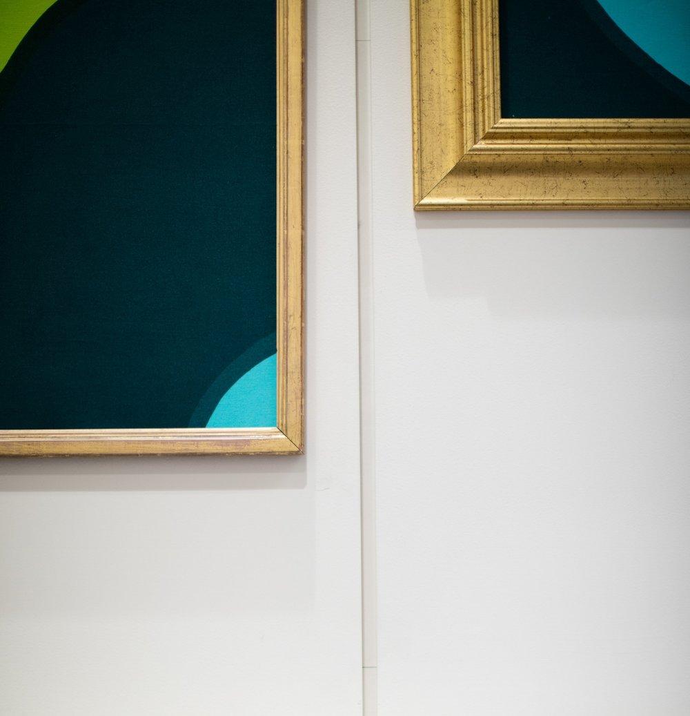 Modern art in gold frames on white wall