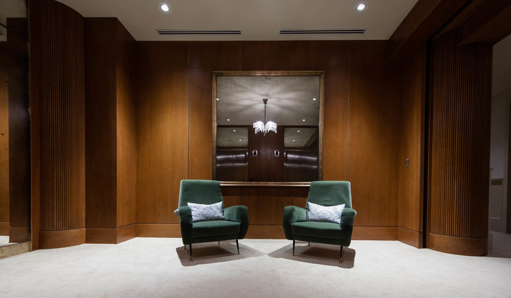 Mid century modern hotel lobby with green velvet chairs and wood walls