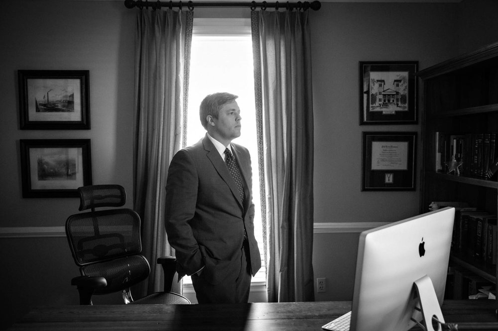 Black and white portrait of lawyer at desk in office