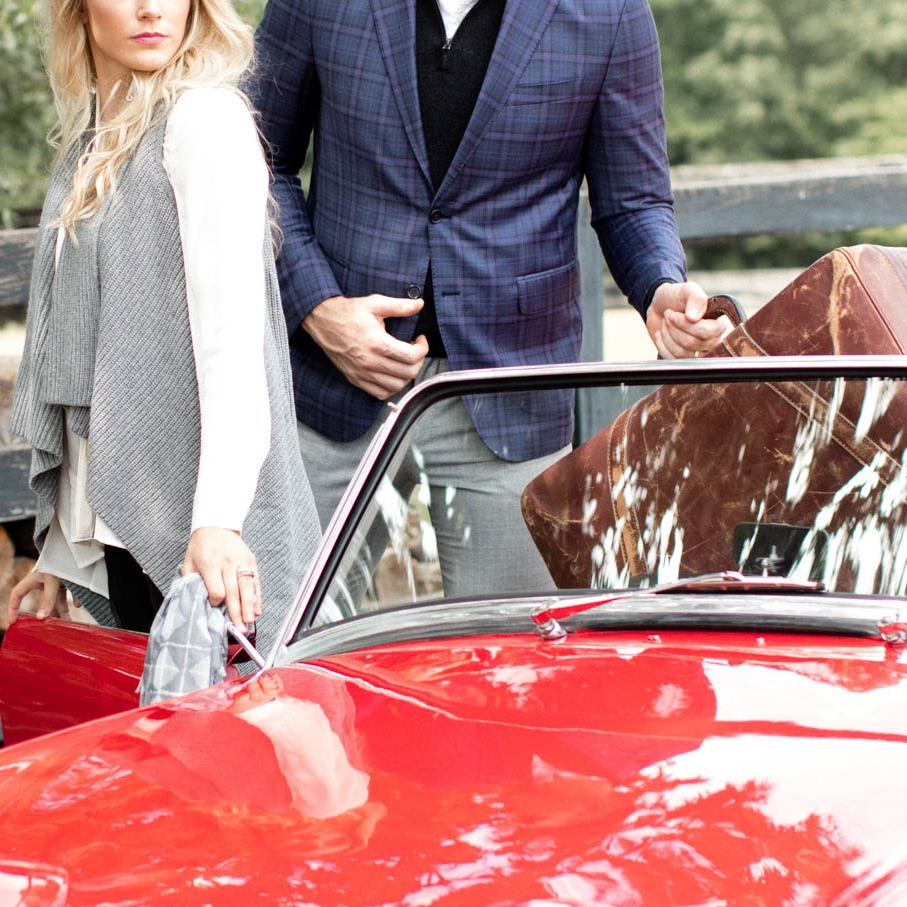Well dressed couple and male in plaid suit getting into red vintage convertible