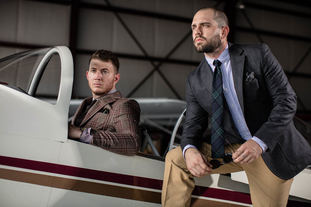 White males in suits at airplane hangar